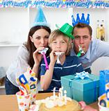 Happy parents celebrating their son's birthday in the kitchen