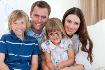 Portrait of family in living-room sitting on sofa together