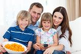 family watching television and eating popcorn at home