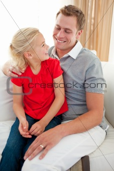 Adorable little girl sitting on sofa with her father
