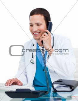 Young male doctor on phone working at a computer