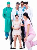 Medical team standing around a pregnant woman 