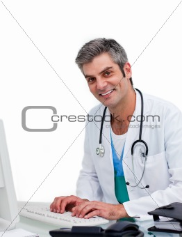Mature male doctor working at a computer