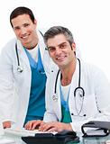Two handsome male doctors working at a computer