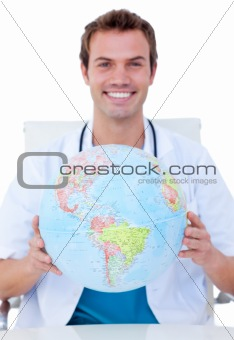 Portrait of a smiling male doctor holding a terrestrial globe