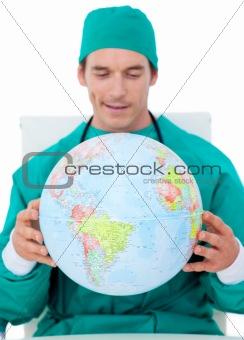 Charming doctor holding terrestrial globe
