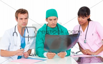 Serious medical team looking at X-ray
