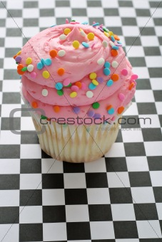 shot of pink sprinkle cupcake on checkered background