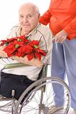 shot of a wife pushing handicap man in wheelchair with flowers