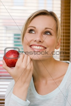 Beautiful Relaxed Woman Holding an Apple Beside Her Face