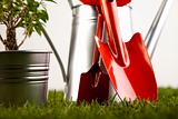Gardening equipment on green grass with plants
