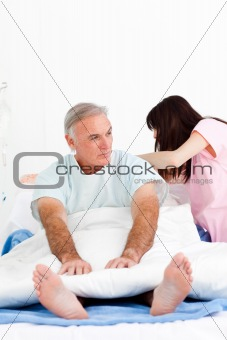 Female nurse adjusting pillows for a senior patient in a hospita