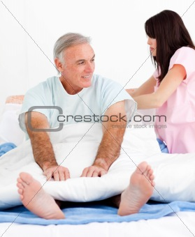 Attentive nurse fixing her patient's bed