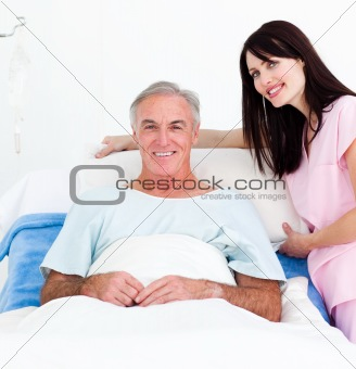 Smiling nurse fixing a senior patient's bed