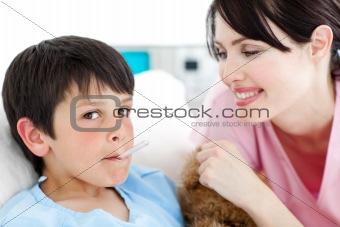 Charming nurse taking little boy's temperature