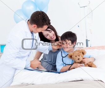 Charming doctor playing with a little boy and his mother