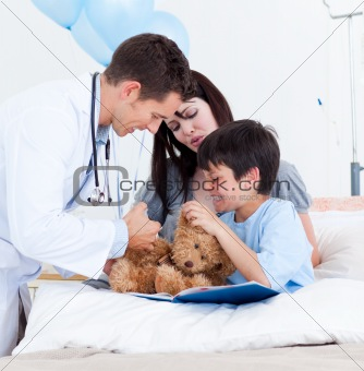 Caucasian doctor playing with a little boy and his mother