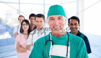 Assertive senior surgeon standing with his colleagues