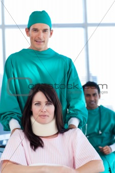 Attractive surgeon carrying a patient on a wheelchair