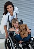 Little girl on a wheelchair holding her teddy bear