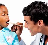 Smiling doctor checking little girl's throat