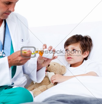 Adorable little boy taking cough medicine