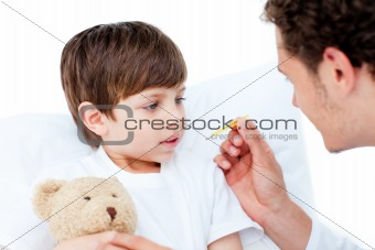 Caucasian doctor taking little boy's temperature