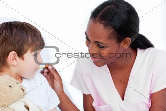 Smiling nurse taking little boy's temperature