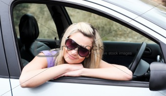 Beautiful young female driver wearing sunglasses