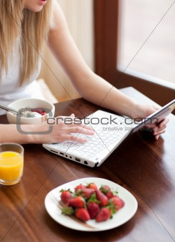 Blond woman using a laptop while having breakfast