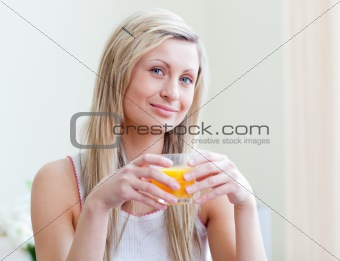 Portrait of an attractive woman drinking an orange juice