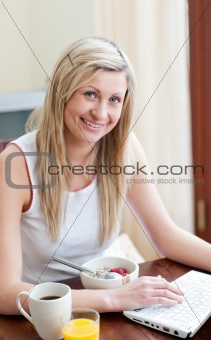 Charming woman using a laptop while having a breakfast