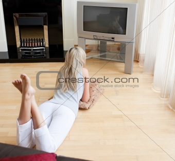 Blond woman watching TV lying on the floor