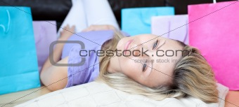 Tired woman after shopping lying on the floor