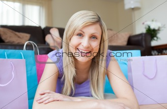 Charming woman lying on the floor after shopping