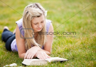 Beautiful woman reading a book in a park