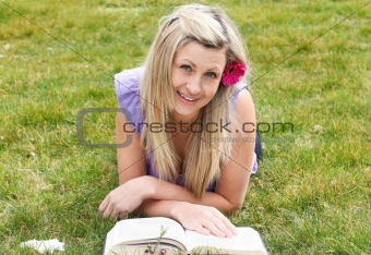 Beautiful woman reading a book lying on the grass