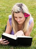 Charming woman reading a book in a park 