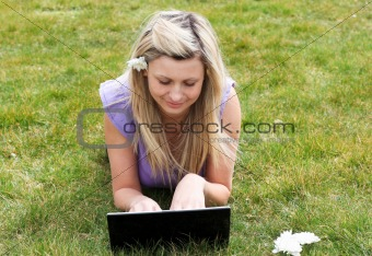 Charming young woman using a laptop lying on the grass