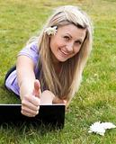Happy young woman using a laptop in a park