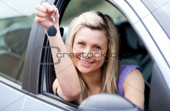 Attractive young driver holding a key after bying a new car
