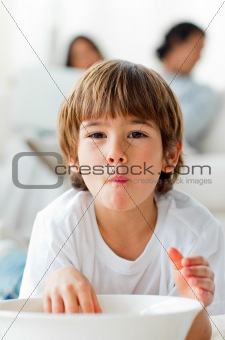 Adorable little boy eating chips lying on the floor