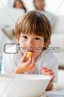 Little boy eating chips lying on the floor in the living-room