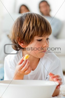 Little boy eating chips lying on the floor