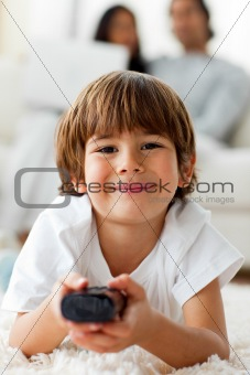 Adorable little boy watching TV lying on the floor