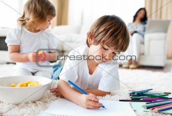 Close-up of siblings eating chips and drawing in the living-room