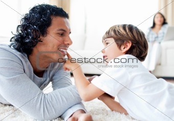 Adorable little boy and his father armwrestling