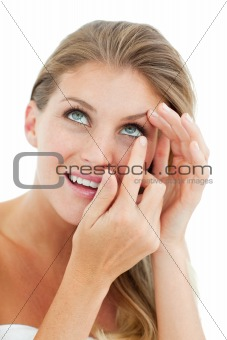 Attractive blond woman putting a contact lens