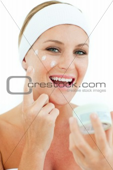 Caucasian woman putting cosmetic cream