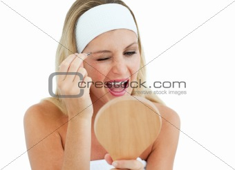 Blond woman using tweezers